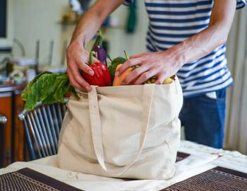 man with bag of groceries unpacking fresh produce onto counter top in kitchen