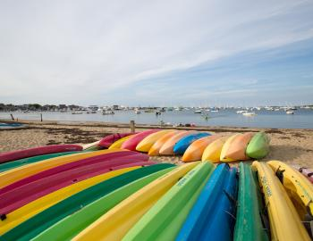 brightly colored kayaks face down in the sand on a beach in nantucket