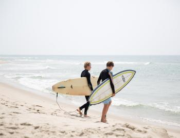 two guys with surfboards heading out to the water of Nantucket beaches
