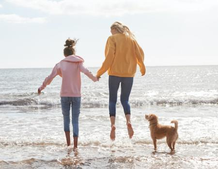 mom and daughter on beach with dog jumping in the water with jeans and sweaters on