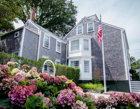 view of historic nantucket home with vibrant flowers and american flag in foreground