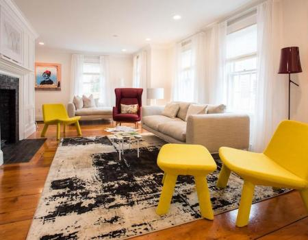 bright yellow chair, beige sofa and other bright furniture in background of bright modern living room