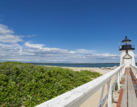 bright blue sky overlooking beach and brant point lighthouse in nantucket