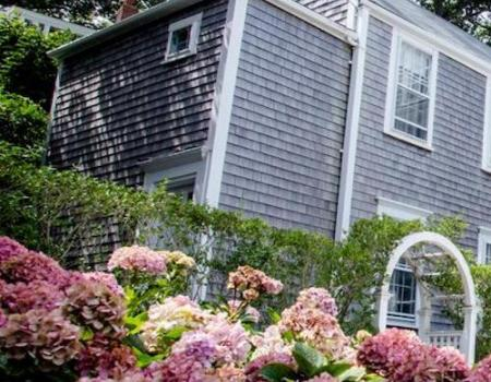 flowers in front of nantucket vacation rental with quintessential shingles
