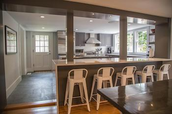 open concept kitchen at 26 pleasant street in downtown nantucket with white counters and backsplash and gray cabinets with modern appliances