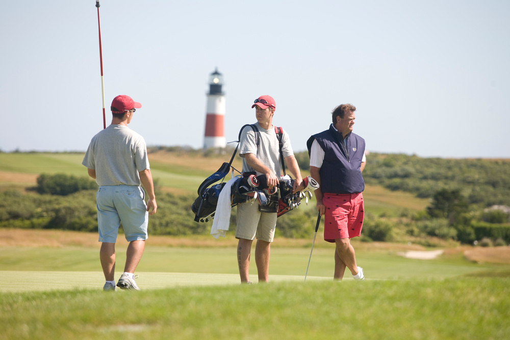 three guys on a golf course on a sunny afternoon with lighthouse in the background