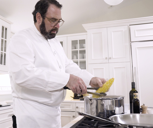 chef in white coat cooking corn on stove in all white kitchen