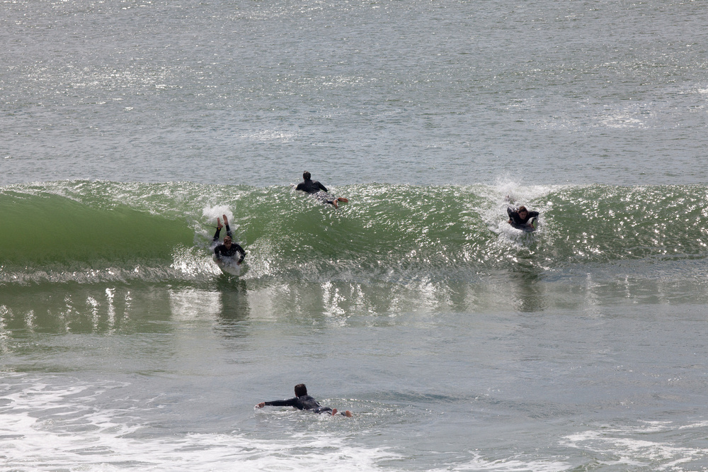 four surfers catching a wave on a nantucket beach