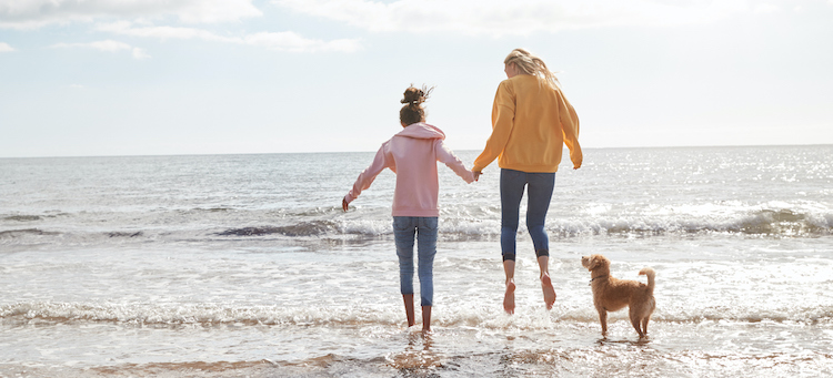 mom daughter and dog on beach